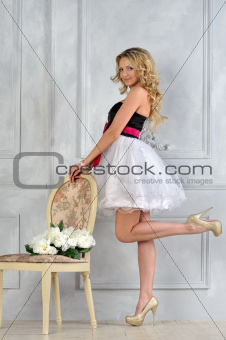 Beautiful blonde woman in fancy dress in luxury interior.
