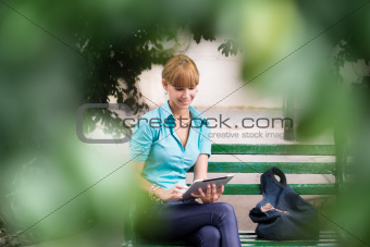 hispanic woman with digital tablet pc on bench