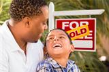 Happy African American Father and Mixed Race Son in Front of Sold Real Estate Sign.
