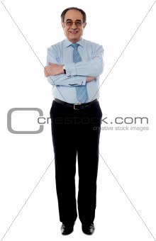 Senior business executive posing with folded arms
