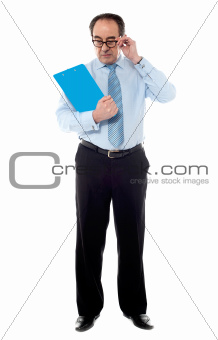 Senior corporate man taking a close look at business documents