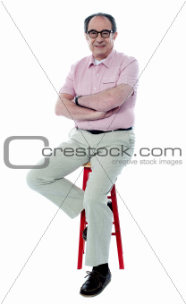 Seated senior man with folded arms