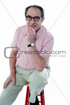 Old man sitting on stool, posing in style
