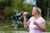 Woman blowing bubbles outdoors