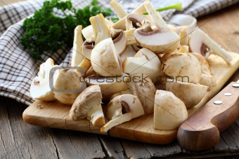 fresh champignons mushrooms, sliced ​​on the board