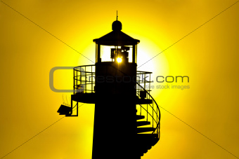 Lighthouse silhouette at yellow sunset