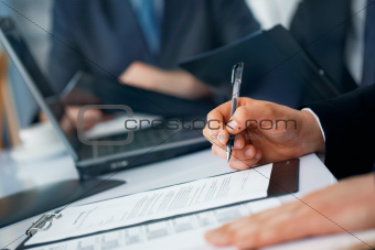 businessman's hands with pen and documents