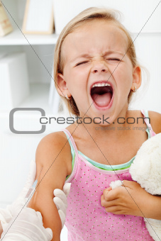 Distressed little girl getting an injection or vaccine
