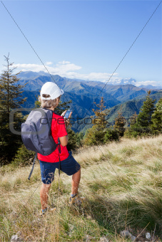 Young boy standing along a mountain path using a  smartphone