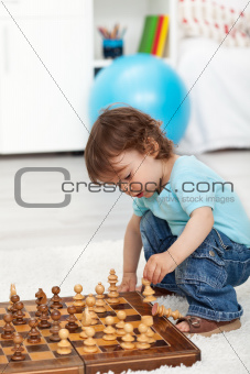 Toddler boy playing with chess pieces