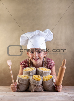 Happy chef child with pasta assortment and kitchen utensils