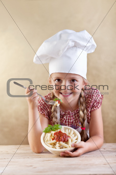 Little chef eating pasta with tomato sauce and basil