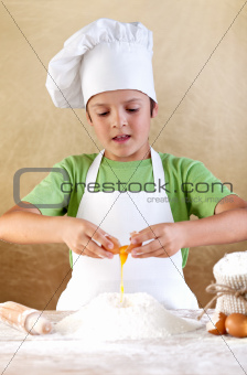 Boy with chef hat preparing the dough