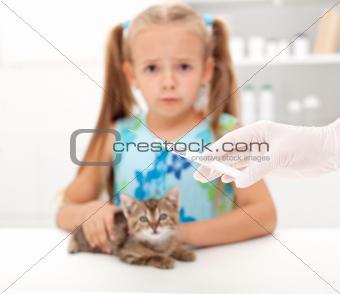 Little girl afraid for her kitten getting a vaccine at the veter