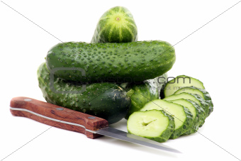 Fresh juicy cucumbers and knife for cutting vegetables.