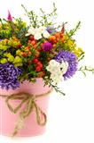 Bouquet of flowers and fruit in pink bucket.