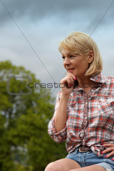A mature lady sitting outdoors