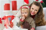smiling young mother and baby eating Christmas cookie