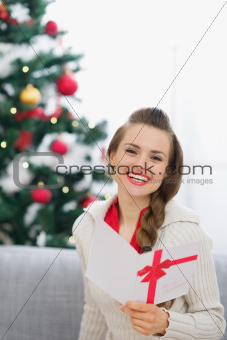 Smiling young woman with Christmas postcard