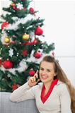 Happy young woman speaking mobile phone near Christmas tree