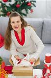 Smiling young woman packing parcel with Christmas gift