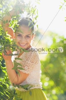 Smiling young woman playing in foliage