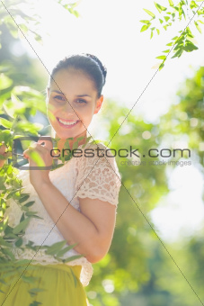 Smiling girl playing in foliage
