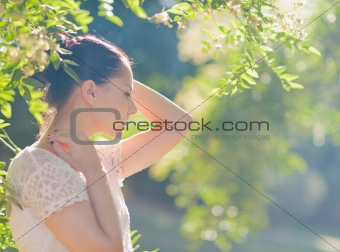 Thoughtful young woman relaxing in forest