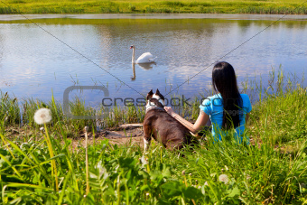 woman with dog sitting on the bank