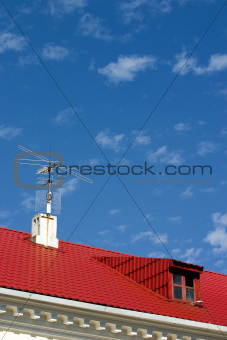 brightly red roof with a dormer on a background blue sky