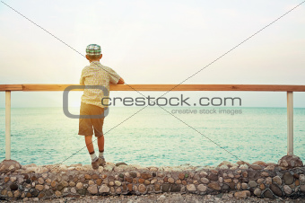 boy standing on quay in the dusk looking at sea