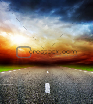 road in field over stormy dark cloudy sky
