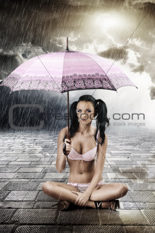 sexy brunette with umbrella, sitting with crossed legs
