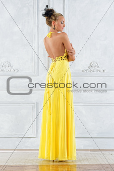 Beautiful blonde woman in a long yellow dress.