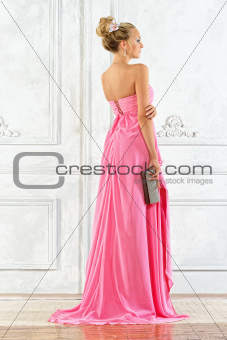 Beautiful blonde woman in a pink evening long dress.