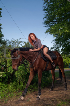 woman with red hair sitting on a horse