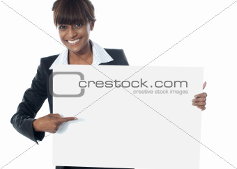 Corporate female executive pointing towards blank banner