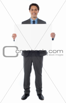 Young businessman holds the blank billboard
