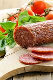 sliced meat sausage salami on wooden board with  green herbs