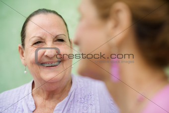 Two elderly women meeting and talking on park bench