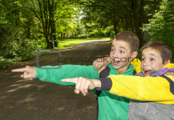 Portrait of two surprised boys, tweens are pointing and hugging