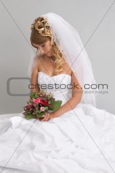 Beautiful bride with stylish make-up and hairdo holding bouquet