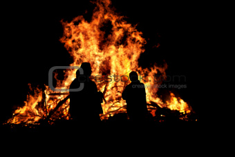 Three persons in front of bonfire