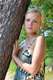 Beautiful blonde woman standing at the tree
