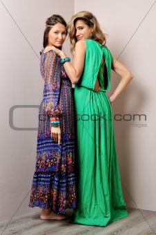 Two beautiful woman in long dresses.