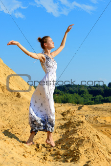 Beautiful woman posing at the sand place.