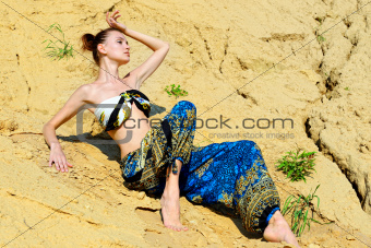 Beautiful woman sitting on the sand
