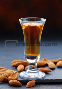 Almond liquor amaretto with whole nuts on a dark background