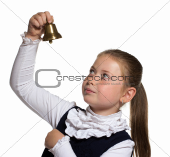 Young school girl looking to golden bell on white background
