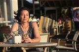 Woman sitting in outdoor cafe with glas of white vine